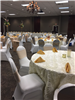 Chairs with white covers are set up at a tables for a reception