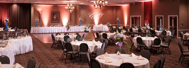 Tables and chairs are set up in the banquet hall for an event