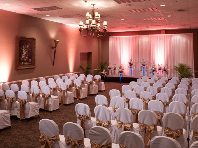 Chairs with covers are set up for a wedding ceremony with pink lighting
