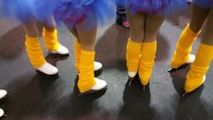People wearing ice skates and tutus